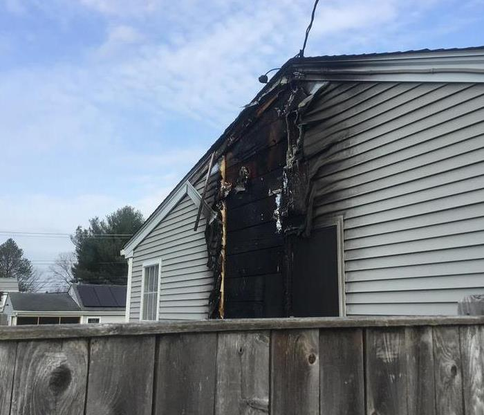 the side of a home with a hole and black charring around it